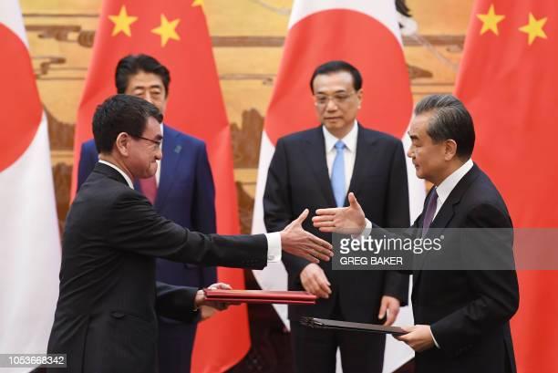Japan's Foreign Minister Taro Kono shakes hands with Chinese Foreign Minister Wang Yi as Japan's Prime Minister Shinzo Abe and Chinese Premier Li...