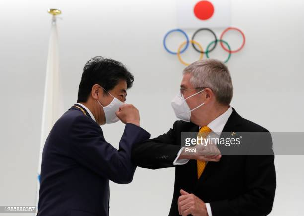 Japan's former Prime Minister Shinzo Abe and Thomas Bach, President of the International Olympic Committee , elbow bump after a ceremony to present...