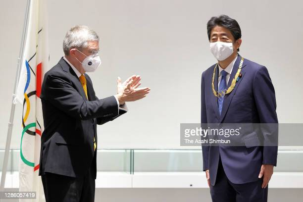 Japan's former Prime Minister Shinzo Abe is applauded by Thomas Bach, President of the International Olympic Committee after presented the Olympic...