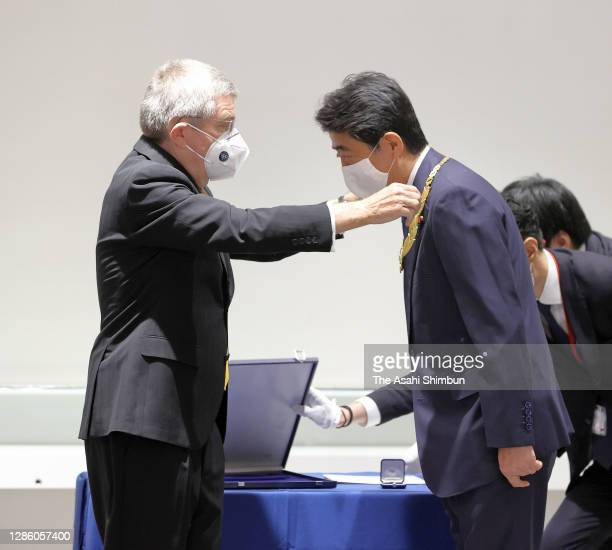 Japan's former Prime Minister Shinzo Abe is presented the Olympic Order from Thomas Bach, President of the International Olympic Committee , during a...