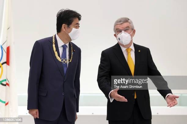 Japan's former Prime Minister Shinzo Abe talks with Thomas Bach, President of the International Olympic Committee after a ceremony to receive the...