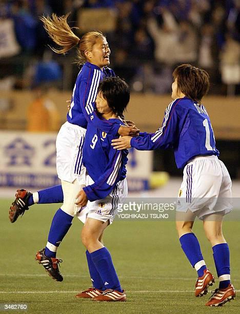 Japan's forward Eriko Arakawa hugs with her teammate Homare Sawa and Mio Otani after she scored a goal during the AFC women's football Olympics...