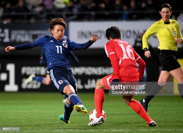 Japan's forward Mina Tanaka fights for the ball with North Korea's defender Kim UnHa during the women's football match between Japan and North Korea...