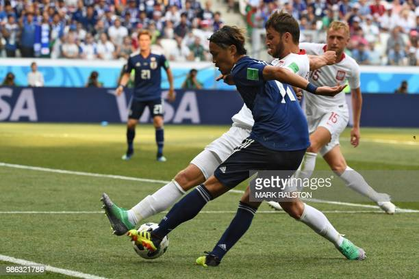 Japan's forward Takashi Usami kicks the ball past Poland's defender Bartosz Bereszynski during the Russia 2018 World Cup Group H football match...