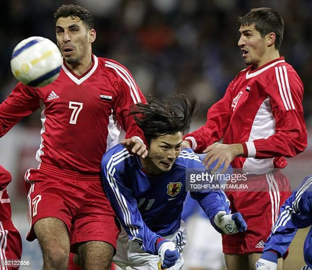 Japan's forward Takayuki Suzuki battles for a ball with Syrian defenders Anas Al Khoja and Ali Dyab during their friendly match in Saitama north of...