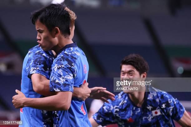 Japan's forward Takefusa Kubo celebrates his opening goal with teammates during the Tokyo 2020 Olympic Games men's group A first round football match...