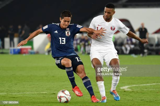Japan's forward Yoshinori Muto is marked by Qatar's midfielder Salem Al Hajri R during the 2019 AFC Asian Cup final football match between Japan and...