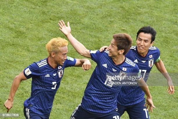 Japan's forward Yuya Osako celebrates with Japan's defender Yuto Nagatomo and Japan's midfielder Makoto Hasebe after scoring their second goal during...