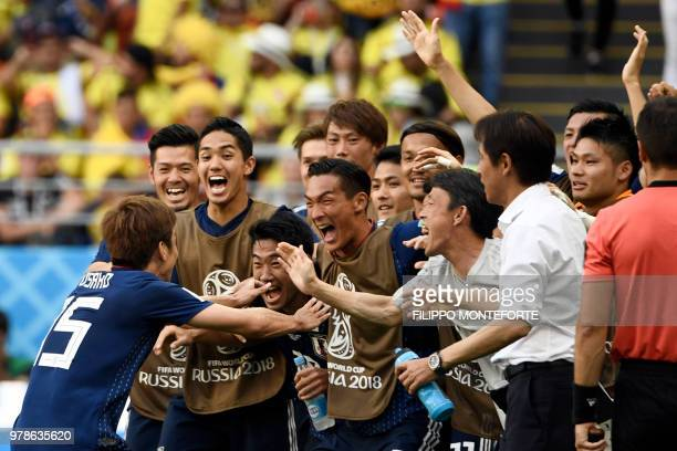 Japan's forward Yuya Osako celebrates with teammates after scoring a goal during the Russia 2018 World Cup Group H football match between Colombia...