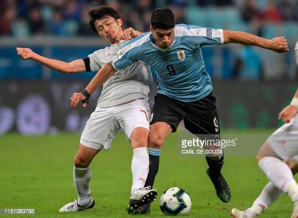 TOPSHOT Japan's Gaku Shibasaki and Uruguay's Luis Suarez battle for the ball during the Copa America football tournament Group C match between...