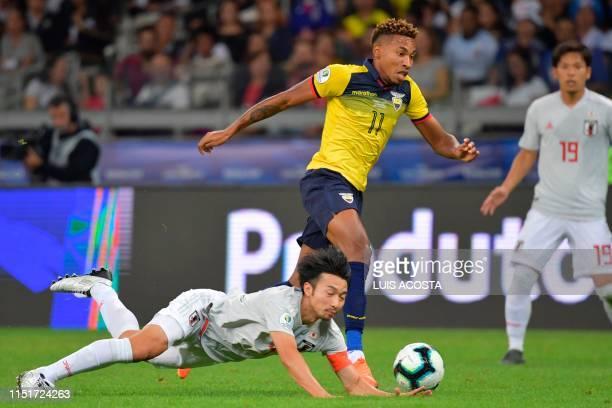 Japan's Gaku Shibasaki falls next to Ecuador's Ayrton Preciado during their Copa America football tournament group match at the Mineirao Stadium in...