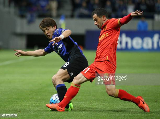 Japan's Gamba Osaka midfielder Ritsu Doan and Australia's Adelaide United forward Sergio Cirio fight for the ball during the AFC Champions League...