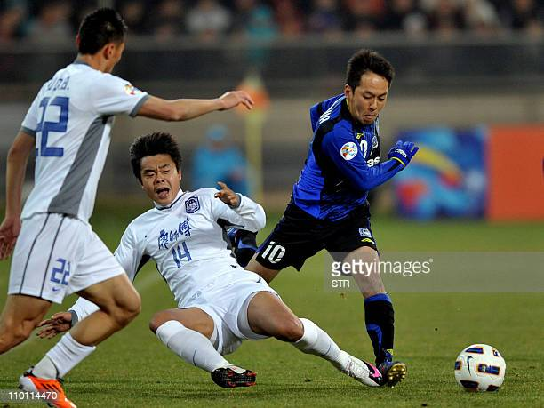 Japan's Gamba Osaka player Takahiro Futagawa fights for the ball against China's Tianjin Teda player Bai Yuefeng during the AFC Champions League...