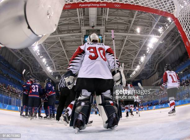 Japan's goalie Akane Konishi looks on Unified Korea's Randi Griffin celebrates with team mates after she scored in the women's preliminary round ice...