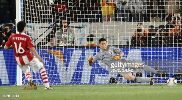 Japan's goalkeeper Eiji Kawashima concedes a kick by Paraguay's midfielder Cristian Riveros in the penalty shoutouts during the 2010 World Cup round...