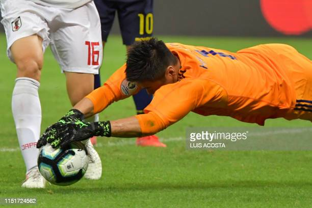 Japan's goalkeeper Eiji Kawashima dives for the ball during the Copa America football tournament group match against Ecuador at the Mineirao Stadium...
