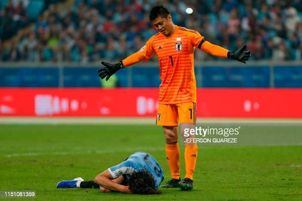Japan's goalkeeper Eiji Kawashima gestures as Uruguay's Edinson Cavani lies on the ground after being fouled at the area during the Copa America...