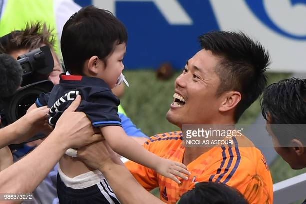 Japan's goalkeeper Eiji Kawashima greets a baby from the crowd after the final whistle during the Russia 2018 World Cup Group H football match...