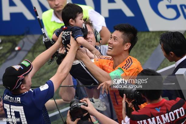 TOPSHOT Japan's goalkeeper Eiji Kawashima greets his son Kensei from the crowd after the final whistle during the Russia 2018 World Cup Group H...