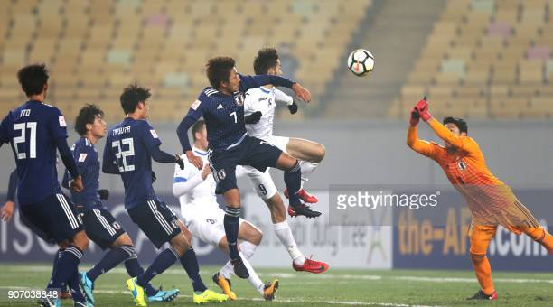 Japan's goalkeeper Ryosuke Kojima defends from an Uzbekistan shot at goal as Japanese players support during their AFC Under23 Championship football...