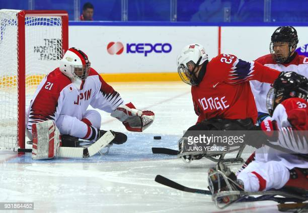 Japan's goalkeeper Shinobu Fukushima and Norway's Jan Roger Klakegg fight for the puck during the ice hockey classification game between Norway and...
