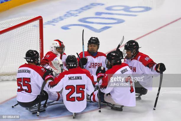 Japan's goalkeeper Shinobu Fukushima and teammates gather before the 2nd period in the ice hockey classification game between Norway and Japan at the...