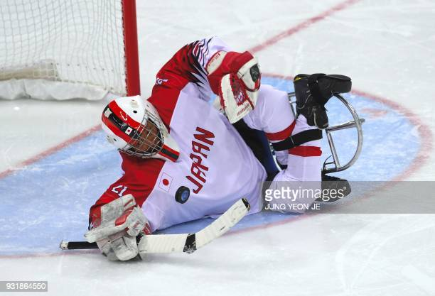 Japan's goalkeeper Shinobu Fukushima makes a save against during in the ice hockey classification game between Norway and Japan at the Gangneung...