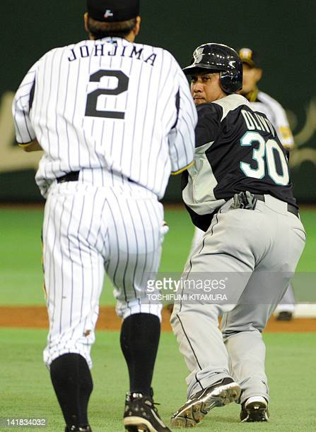 Japan's Hanshin Tigers first baseman Kenji Johjma chases US Major League baseball team Seattle Mariners catcher Miguel Olivo between first and second...