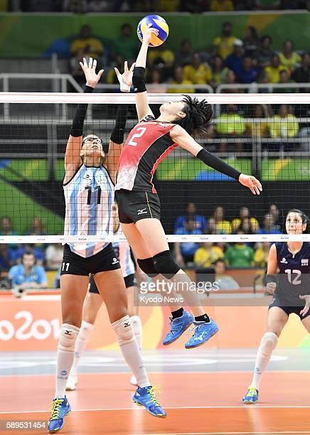 Japan's Haruka Miyashita taps the ball over the net as Argentina's Julieta Lazcano tries to block during the third set of their preliminaryround...
