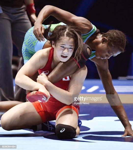 Japan's Haruna Okuno holds the leg of Nigeria's Odunayo Folasade Adekuoroye in the women's 55kilogram final at the world wrestling championships in...
