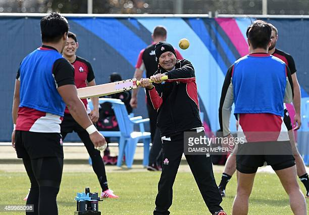Japan's head coach Eddie Jones hits a ball with a cricket bat as he takes a team training session at Warwick School in central England on September...