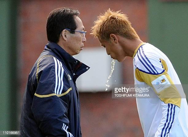 Japan's head coach Takeshi Okada walks beside Keisuke Honda prior to the training match against Zimbabwe at the Outeniqua Stadium in George on June...