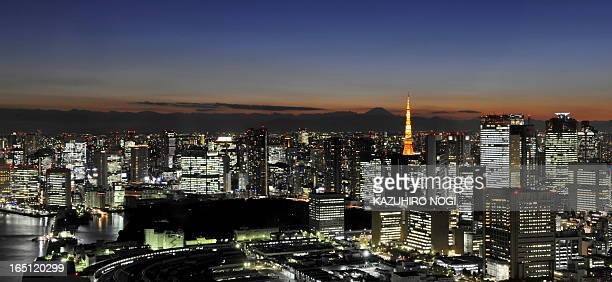 Japan's highest mountain Mount Fuji and Tokyo tower are seen behind the Tokyo's business area at sunset on January 26 2010 The Tokyo Tower stands at...