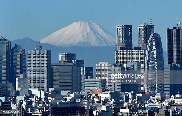 Japan's highest mountain Mount Fuji is seen behind the skyline of the Shinjuku area of Tokyo on December 6 2014 Tokyo stocks closed at a sevenyear...