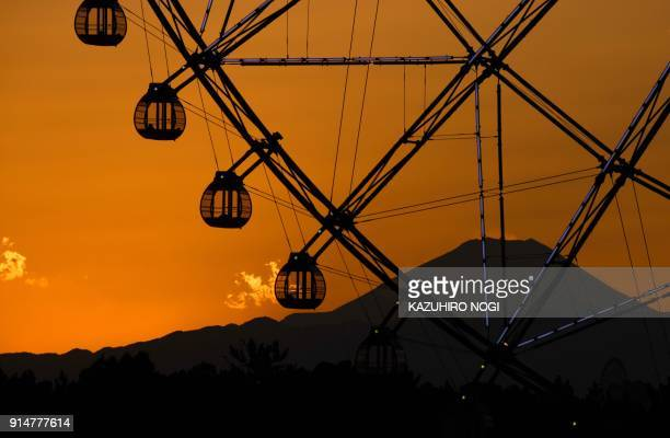 TOPSHOT Japan's highest mountain Mt Fuji is seen in the background over a ferris wheel during sunset at Kasai Rinkai Park in Tokyo on February 6 2018...
