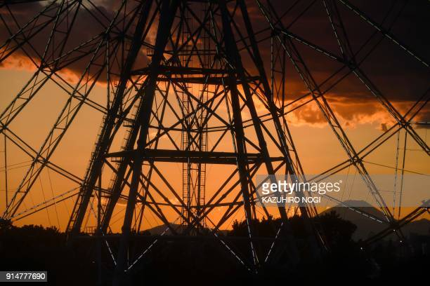 Japan's highest mountain Mt Fuji is seen in the background over a ferris wheel during sunset at Kasai Rinkai Park in Tokyo on February 6 2018 / AFP...