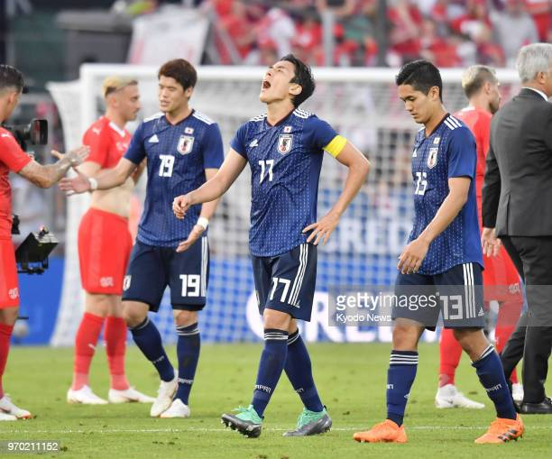 Japan's Hiroki Sakai Makoto Hasebe and Yoshinori Muto look dejected after their team lost 20 to Switzerland in a preWorld Cup friendly in Lugano...