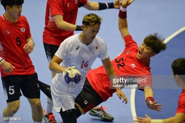 Japan's Hiroki Shida controls the ball past South Korea's players during the men's handball preliminary Group B match between South Korea and Japan...