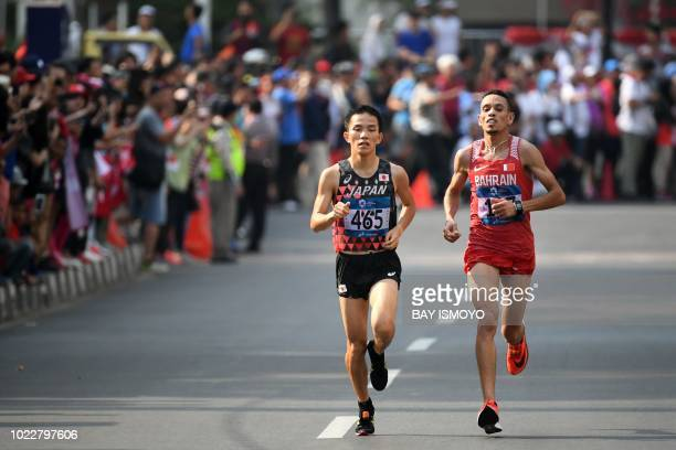 Japan's Hiroto Inoue and Bahrain's Elhassan Elabbassi compete in the men's marathon athletics event during the 2018 Asian Games in Jakarta on August...