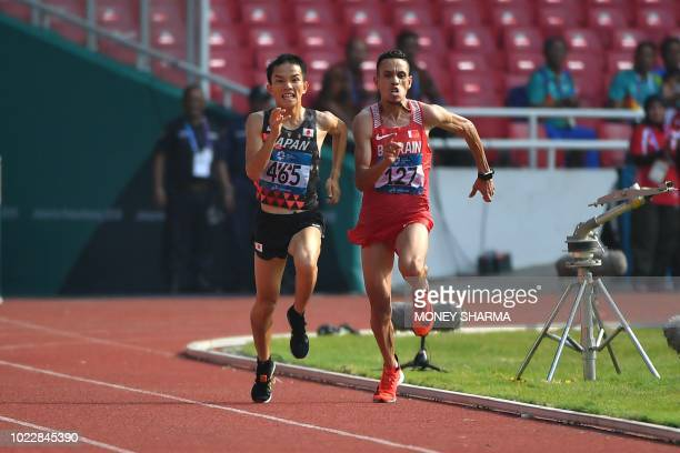 Japan's Hiroto Inoue and Bahrain's Elhassan Elabbassi run toward the finish line in the men's marathon athletics event during the 2018 Asian Games in...