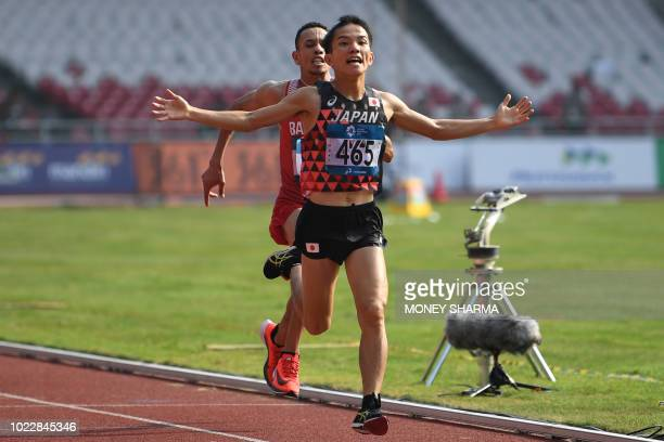 Japan's Hiroto Inoue crosses the finish line ahead of Bahrain's Elhassan Elabbassi to win the men's marathon athletics event during the 2018 Asian...