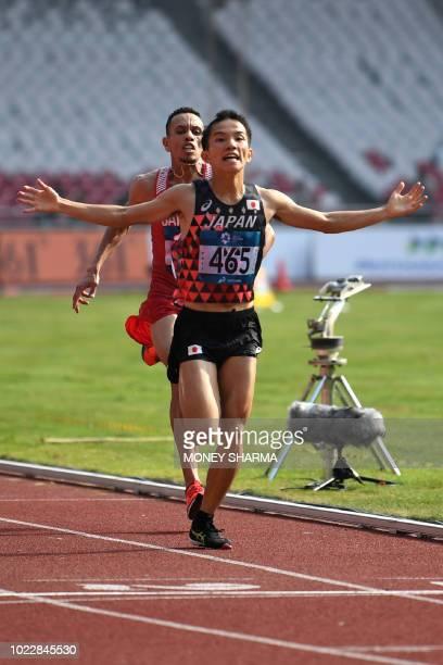 Japan's Hiroto Inoue gestures as he crosses the finish line ahead of Bahrain's Elhassan Elabbassi to win the men's marathon athletics event during...