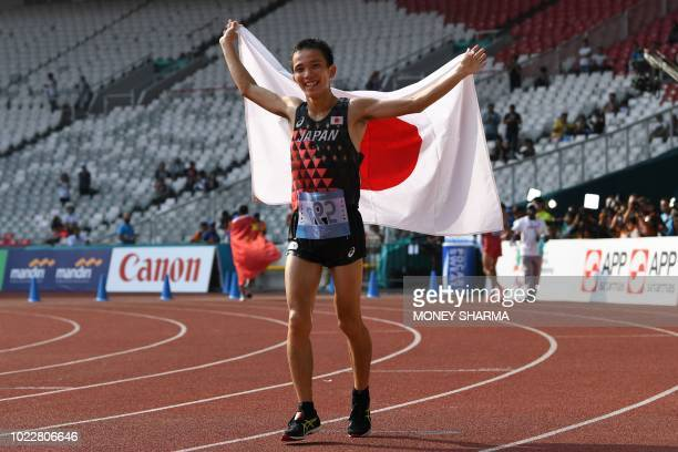 Japan's Hiroto Inoue holds his national flag after winning the men's marathon athletics event during the 2018 Asian Games in Jakarta on August 25,...
