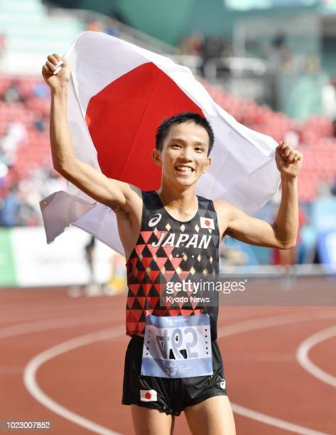 Japan's Hiroto Inoue raises his country's flag after winning Japan's first gold in 32 years in the men's marathon at the Asian Games in Jakarta on...