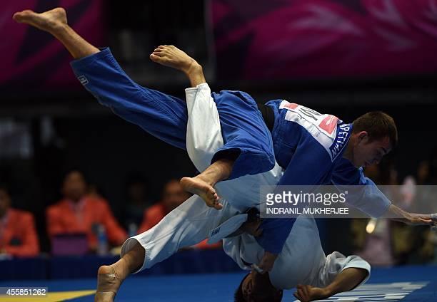 Japan's Hiroyuki Akimoto flips Kazakhstan's Dastan Ykybayev at the Dowon Gymnasium during the men's 73kg judo elimination round of the 2014 Asian...