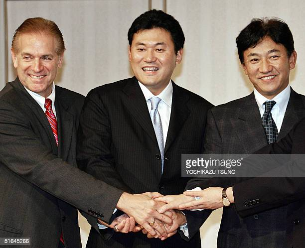 Japan's internet shopping mall operator Rakuten's president Hiroshi Mikitani join hands with the team's general manager Marty Kuehnart and manager...
