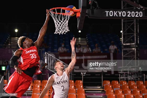 Japan's Ira Brown jumps and scores past Latvia's Karlis Lasmanis during the men's quarter final 3x3 basketball match between Latvia and Japan at the...