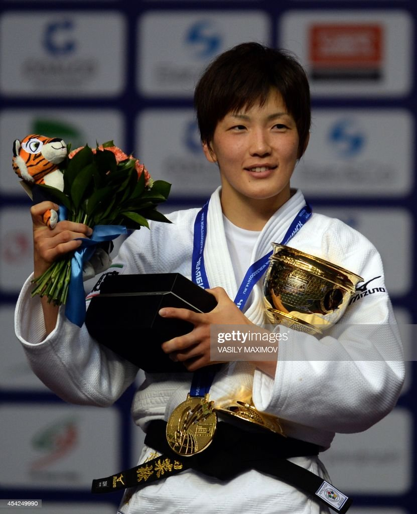 Japan's judoka Nae Udaka poses with the gold medal and a cup after she won the under 57 kg category competition at the IJF World Judo Championship in Chelyabinsk on August 27, 2014.