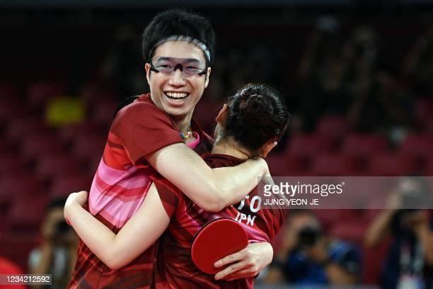 Japan's Jun Mizutani and Mima Ito celebrate after beating China's Xu Xin and Liu Shiwen in their mixed doubles table tennis final match at the Tokyo...
