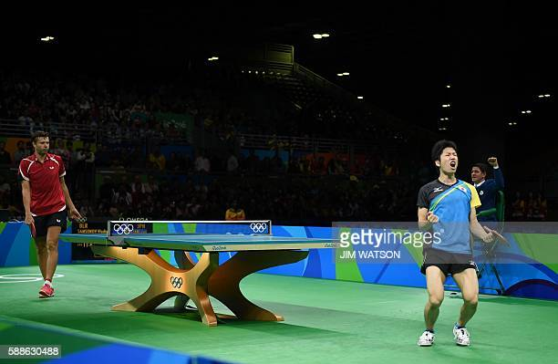 Japan's Jun Mizutani celebrates after a point against Belarus' Vladimir Samsonov in their men's singles bronze medal table tennis match at the...